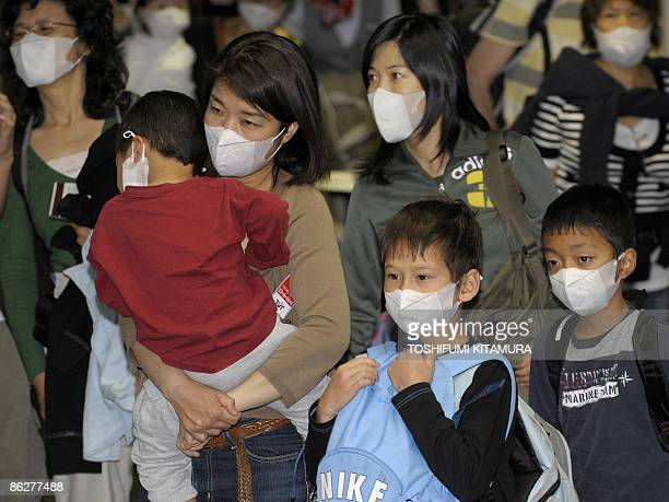 Mother and her children wearing masks leave the plane after it arrived from Mexico City via Vancouver in Canada, at Tokyo's Narita International...