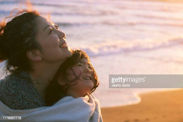 mother and her daughter are holding together in front of the beach - asia pacífico fotografías e imágenes de stock