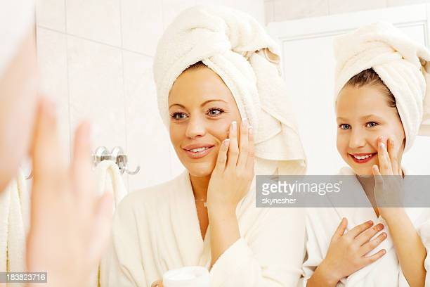 Mother and her daughter are putting on face cream.