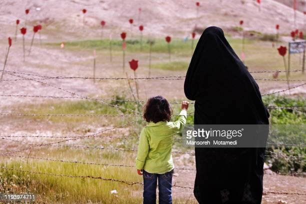 mother and her daughter are visiting the place which iran iraq war happend there - syria stock pictures, royalty-free photos & images