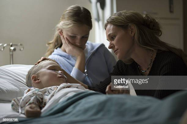 mother and her daughter consoling her son in the hospital - girl in hospital bed sick stock photos and pictures