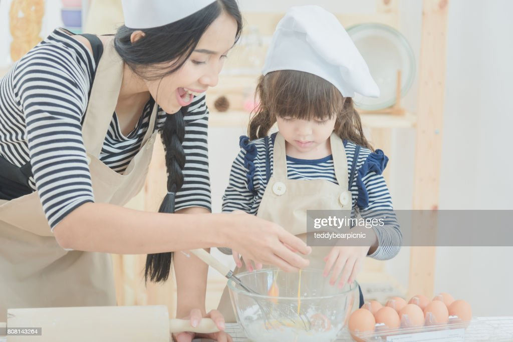 mother and her daughter cooking together to make a cake in kitchen room : Stock Photo