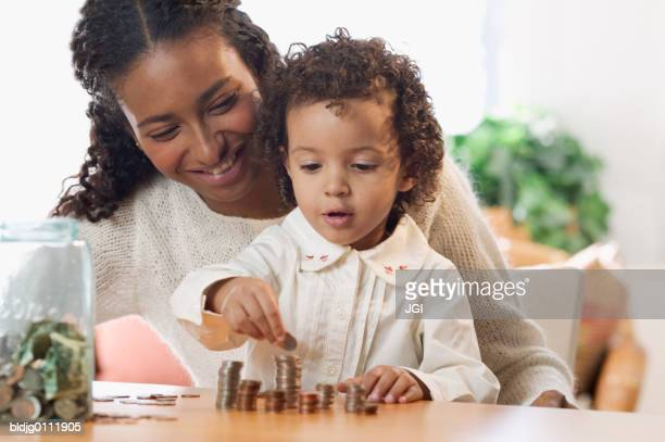 Mother and her daughter counting coins
