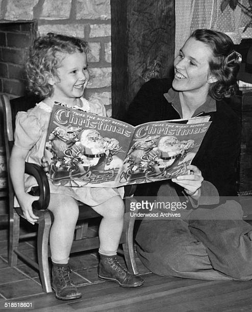 A mother and her daughter having great fun reading the book 'Twas The Night Before Christmas' together Paducah Kentucky early 1940s