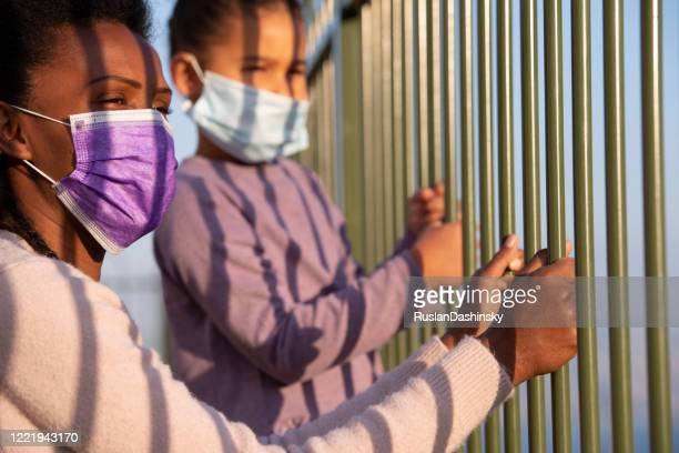 mother and her daughter in face masks looking away through the fence rods. coronavirus pandemic concept. - child behind bars stock pictures, royalty-free photos & images