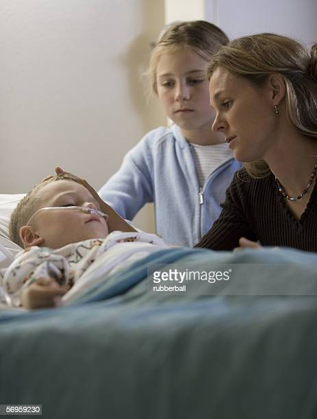 Mother and her daughter looking at her son in the hospital