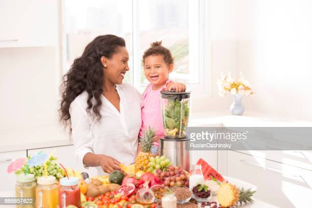 mother and her daughter making fruit juices at kitchen. - mint plant family stock pictures, royalty-free photos & images