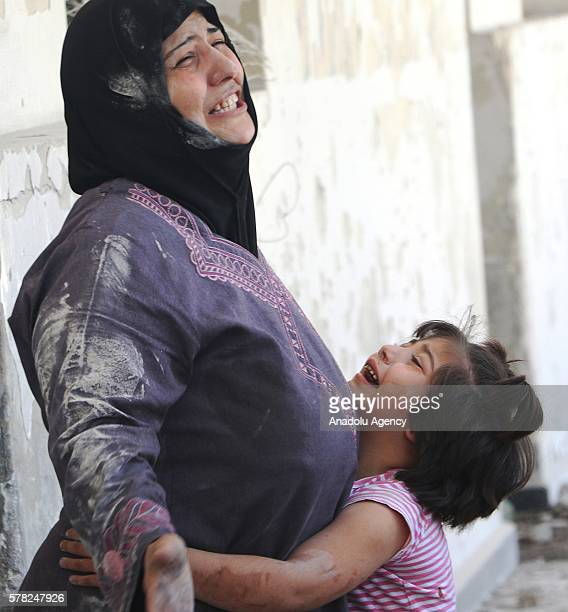 Mother and her daughter mourn after the airstrikes carried out by Russian and Syrian war planes targeted a school in which refugees take shelter at...