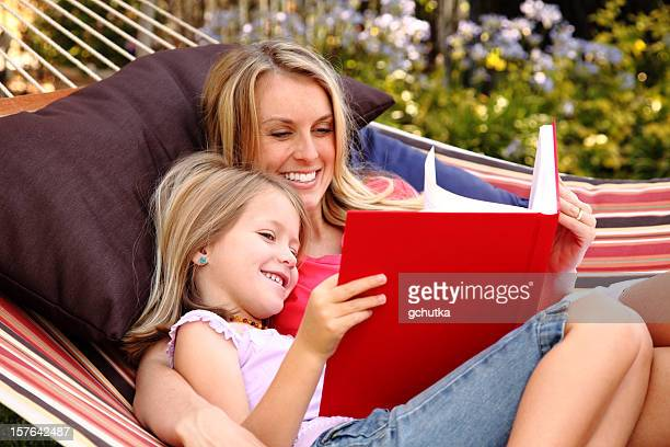 A mother and her daughter reading a big book in a hammock