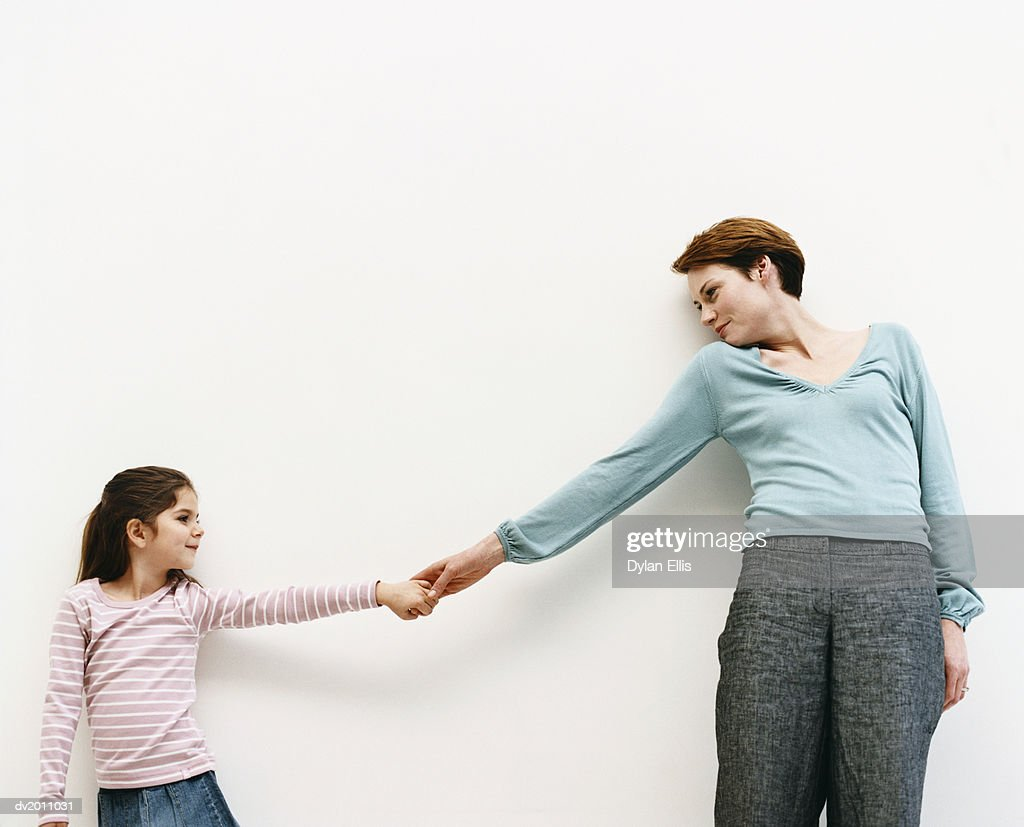 Mother and Her Daughter Stand by a Wall, Reaching Out and Holding Hands : Stock Photo