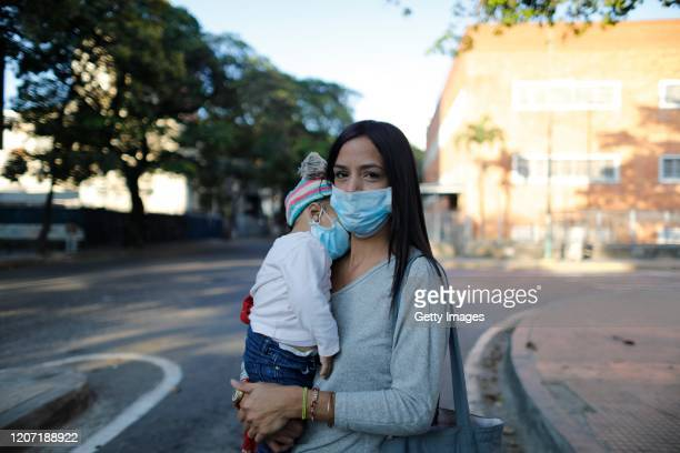 Mother and her daughter wear medical masks before going to work on March 14, 2020 in Caracas, Venezuela. Delcy Rodriguez, Vice President of...
