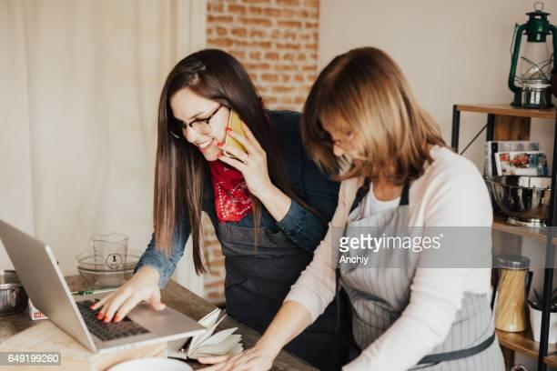 Madre y su hija trabajando juntos en la cocina.