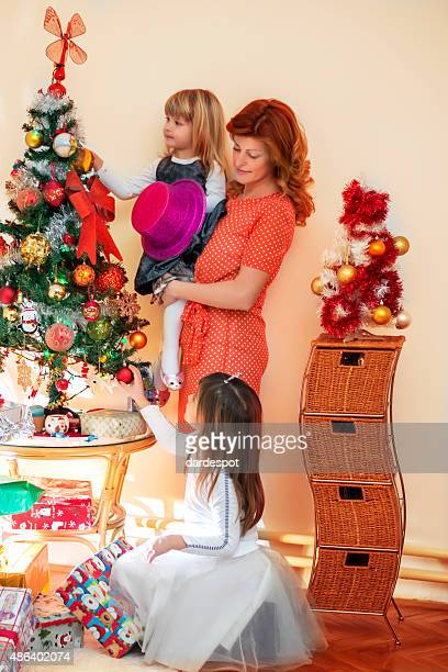 Mother and her daughters by a Christmas Tree