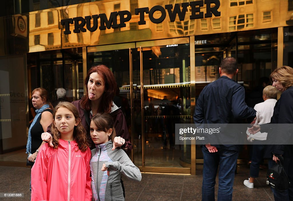 A mother and her daughters express their opinion of Donald Trump outside of Trump Towers in Manhattan October 8, 2016 in New York City. The Donald Trump campaign has faced numerous calls for him to step aside after a recording from 2005 revealed lewd comments Trump made about women.