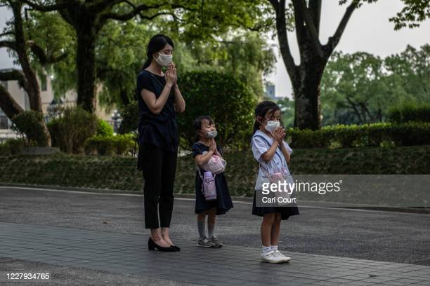 A mother and her daughters pray at the Students Peace Monument on the 75th anniversary of the Hiroshima atomic bombing on August 6 2020 in Hiroshima...