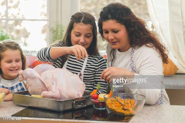 mother and her daughters preparing stuffed turkey for thanksgiving day - stuffing stock photos and pictures