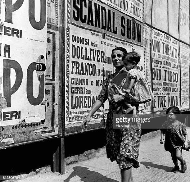 Mother and her daughters walk down the street past large posters advertising scandal shows in Naples, Italy. August 1944.