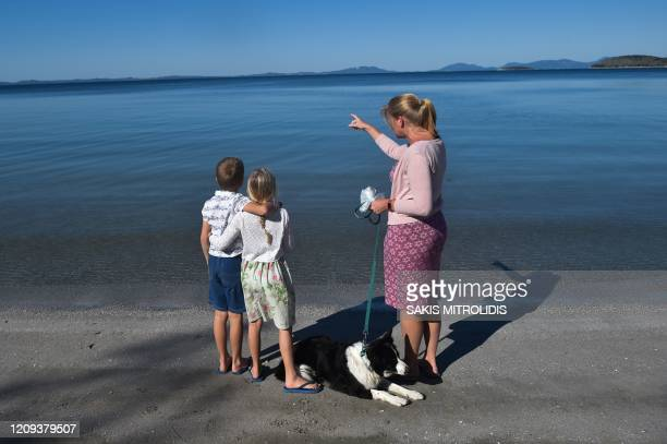 Mother and her kids from England watch the sea in a camping at Igoumenitsa, western Greece on April 8, 2020. - Near the port of Igoumenitsa, in a...