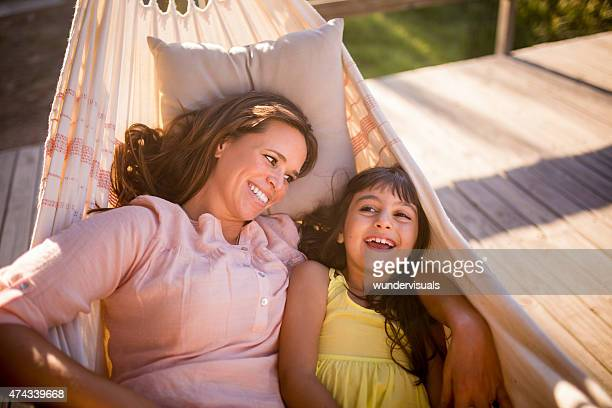 Mother and her laughing daughter lying together in a hammock