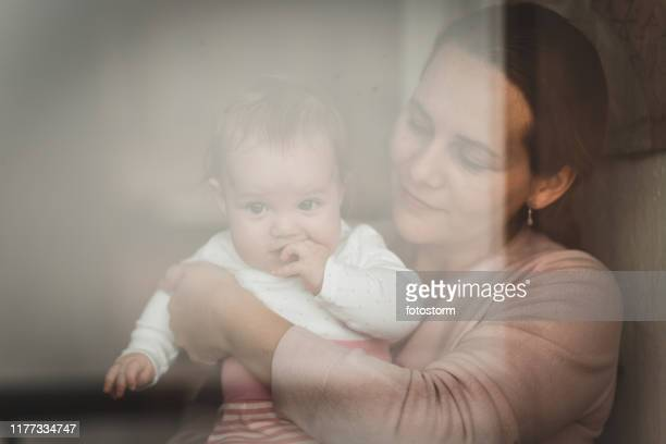 mother and her little baby looking through the window - photographed through window stock pictures, royalty-free photos & images
