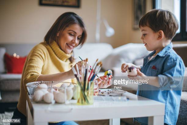mother and her little boy painting easter eggs - tempera painting stock pictures, royalty-free photos & images