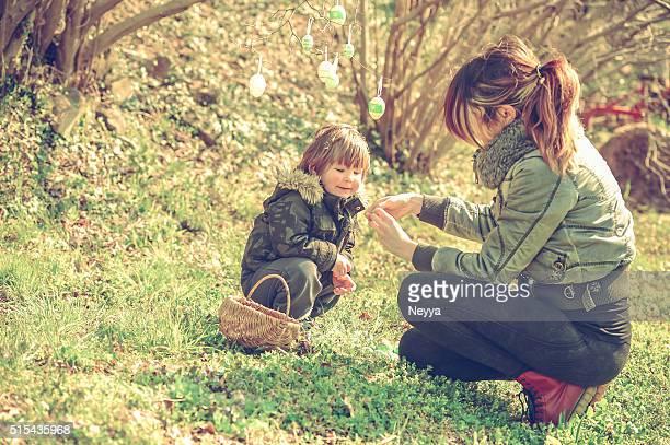 Mãe e seu pequeno Menino com ovos de Páscoa ao ar livre