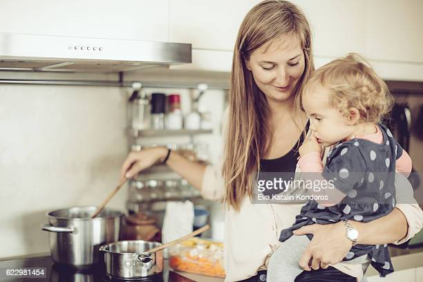 Mother and her little daughter are cooking in the kitchen
