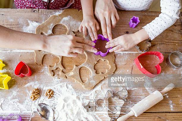 Mother and her little daughter cutting out cookies together, close-up