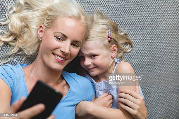 Mother and her little daughter lying on the floor taking selfie with smartphone