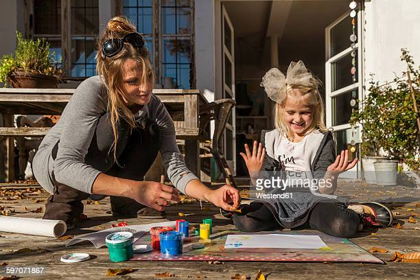 Mother and her little daughter painting with finger colours on the terrace