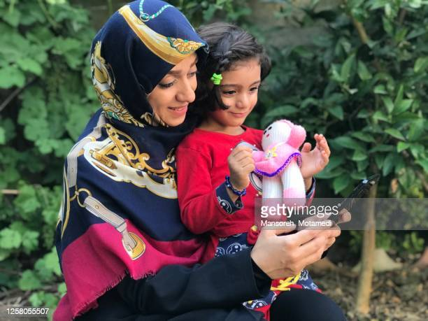 mother and her little girl talking via video call - iranian culture stock pictures, royalty-free photos & images