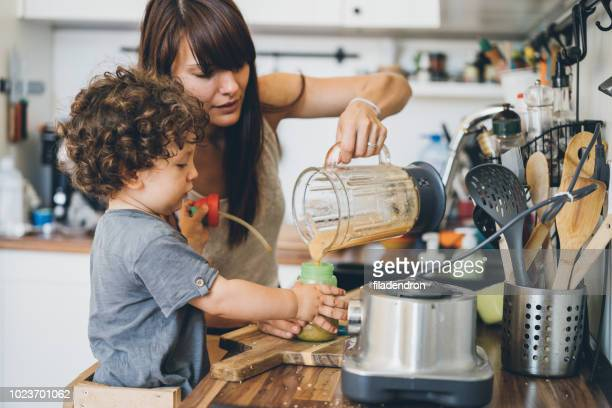 mother and her little son preparing healthy smoothie - appliance stock pictures, royalty-free photos & images