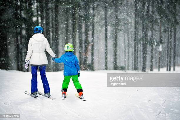 Mother and her little son skiing on snowy day