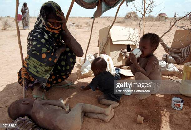 Mother and her malnourished children sit in a shelter they built close to a clinic in the desert April 13, 2000 in Danan, Ogaden Province in...