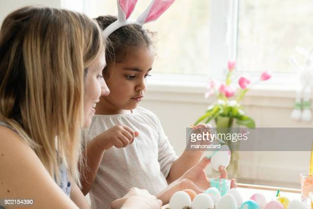 mother and her mixed race daughter painting easter eggs. - happy easter mom stock pictures, royalty-free photos & images
