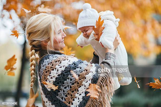 Mother and her newborn son in autumn park