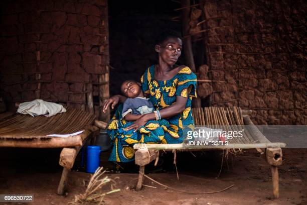 TOPSHOT A mother and her sick child wait at a makeshift paediatric health centre as an outbreak of malaria hit their village on June 12 2017 in Muma...