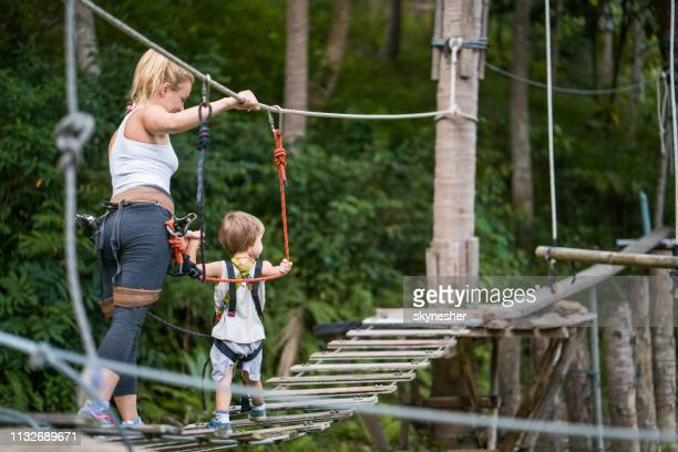 mother and her small son walking during canopy tour in nature. - sports equipment stock pictures, royalty-free photos & images