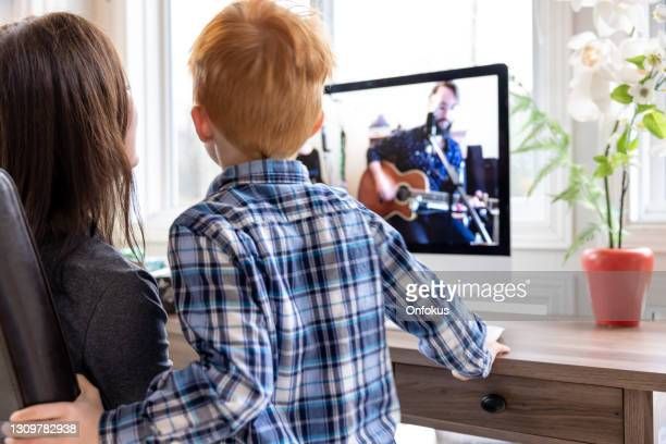 a mother and her son are watching an online music concert from home for her birthday during covid-19 pandemic - performance group stock pictures, royalty-free photos & images