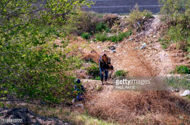A mother and her son cross the Rio Grande between El Paso Texas and Ciudad Juarez Mexico to claim asylum in the United States on March 19 2019...