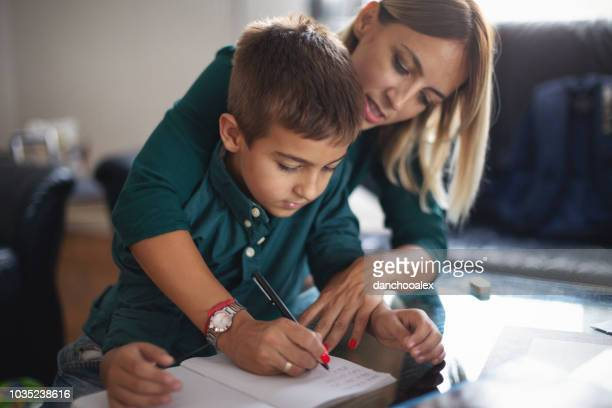 mother and her son doing homework together - struggle stock pictures, royalty-free photos & images