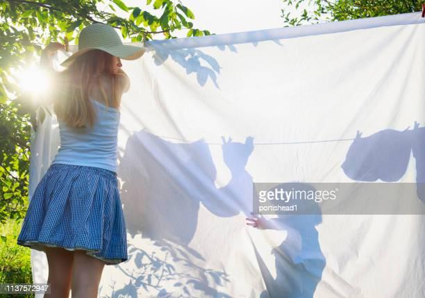 母と彼女の息子は衣類のラインで洗濯をぶら下げます - 物干し ストックフォトと画像