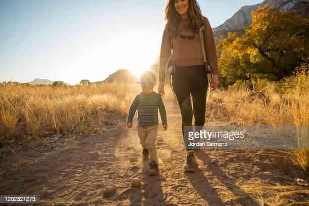 a mother and her son hiking a scenic trail at sunset - erwachsener über 30 stock-fotos und bilder