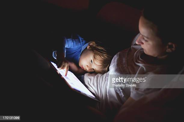 mother and her son looking at a tablet in the dark - image stock pictures, royalty-free photos & images