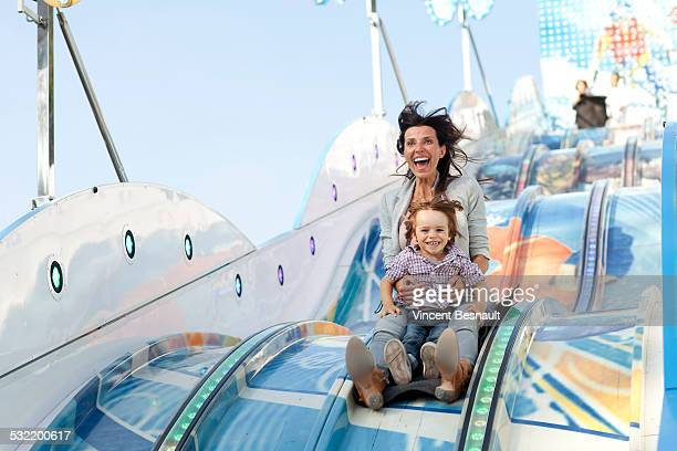 Mother and her son on a slide at the carnival