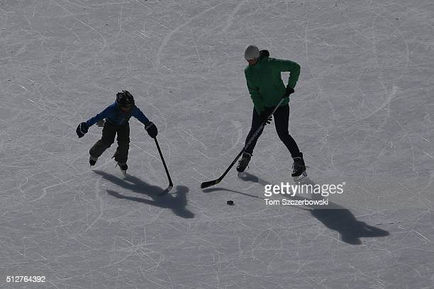 A mother and her son practice on an ice pad adjacent to outdoor shinny hockey action during the 7th Annual Lake Louise Pond Hockey Classic on the...