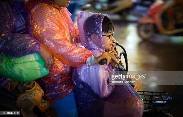 A mother and her son ride on a moped through rainy Hanoi on October 30 2016 in Hanoi Vietnam