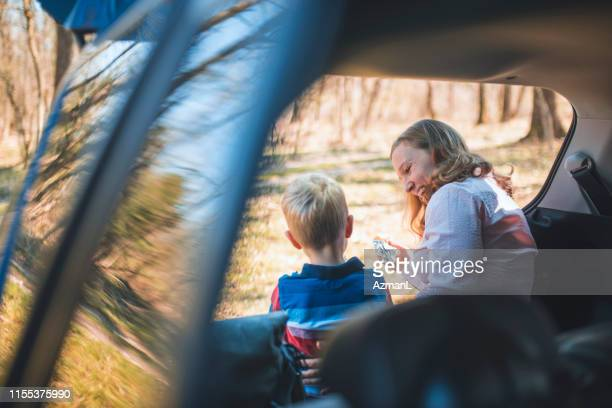 mother and her son sitting in a car trunk and eating sandwich - affettuoso foto e immagini stock