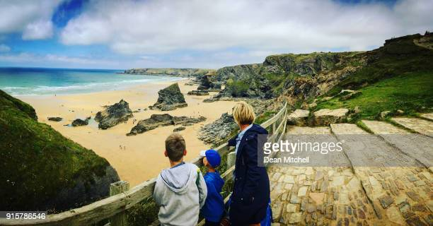 mother and her sons looking at the beautiful beach view - cornovaglia foto e immagini stock