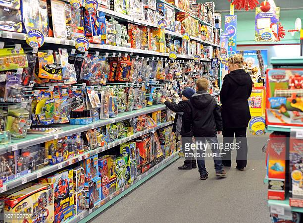 A mother and her sons walk past the shelves of La Grande Recre toys departement store in the French northern city of BruaylaBuissiere on November 20...